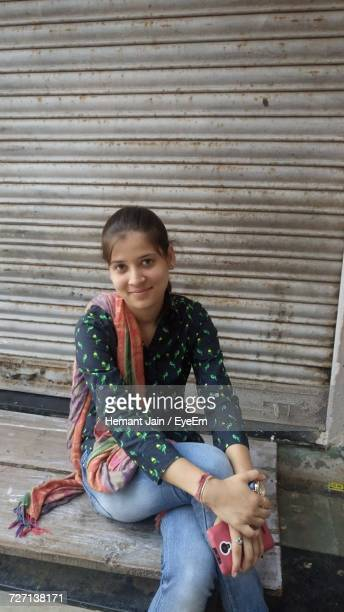 portrait of smiling young woman holding mobile phone sitting against shutter - one young woman only stock pictures, royalty-free photos & images