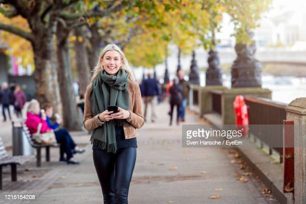 portrait of smiling young woman holding mobile phone while walking on footpath - scarf stock pictures, royalty-free photos & images