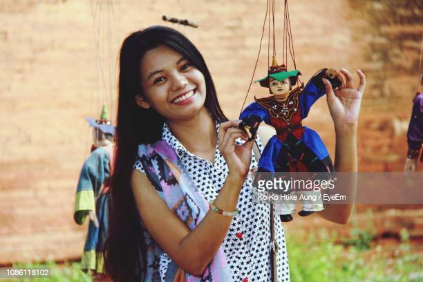 portrait of smiling young woman holding puppet on field - ko ko htike aung stock pictures, royalty-free photos & images