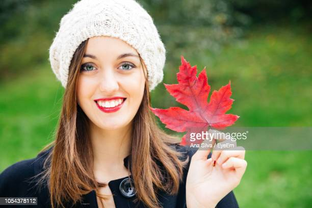 Portrait Of Smiling Young Woman Holding Red Autumn Leaf