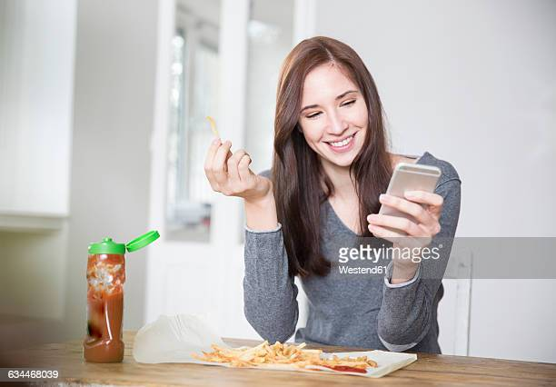 Portrait of smiling young woman holding smartphone while eating French fries with ketchup