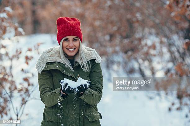 Portrait of smiling young woman holding snow on field