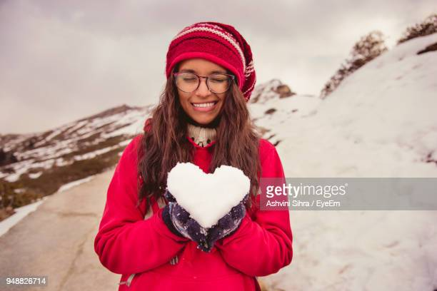 portrait of smiling young woman holding snow on mountain - south asia stock pictures, royalty-free photos & images