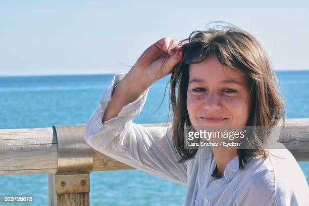 Portrait Of Smiling Young Woman Holding Sunglasses Against Sea