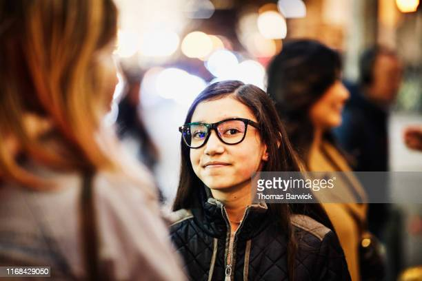 Portrait of smiling young woman holiday shopping with friend on winter evening