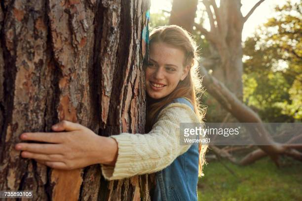 portrait of smiling young woman hugging tree trunk at backlight - tree hugging stock pictures, royalty-free photos & images