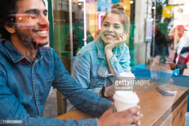 portrait of smiling young woman in a coffee shop looking at young man - flirtare foto e immagini stock