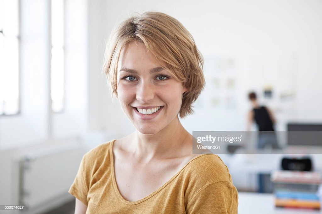 Portrait of smiling young woman in a creative office : Stock Photo