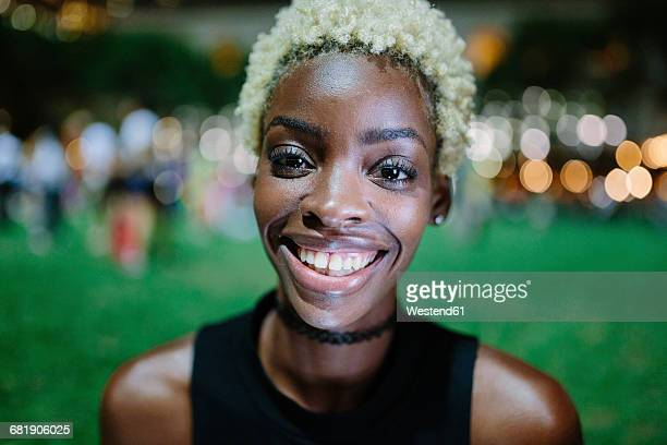 Portrait of smiling young woman in a park at night