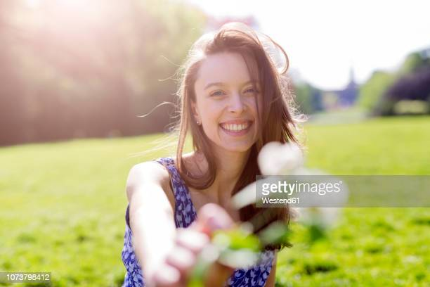 portrait of smiling young woman in a park holding flowers - frühling stock-fotos und bilder