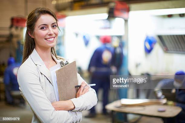 Portrait of smiling young woman in a sculptor's workshop