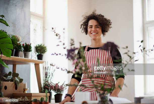 portrait of smiling young woman in a small shop with plants - artisan photos et images de collection