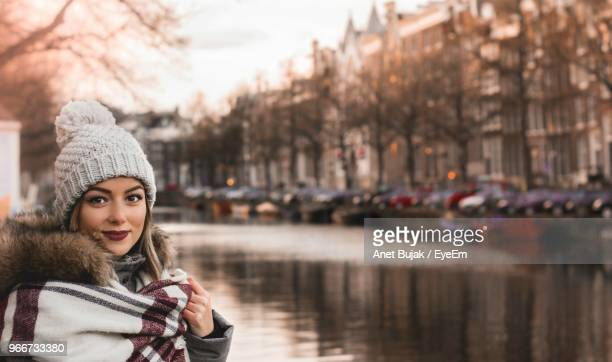 Portrait Of Smiling Young Woman In City During Winter