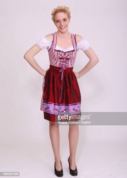 portrait of smiling young woman in dirndl standing against white background - traditional clothing stock pictures, royalty-free photos & images