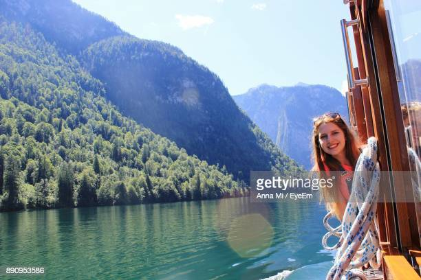 Portrait Of Smiling Young Woman In Ferry Boat On Lake Against Mountains
