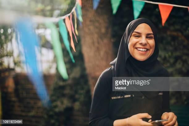 portrait of smiling young woman in hijab holding mobile phone at backyard - middle eastern ethnicity stock pictures, royalty-free photos & images