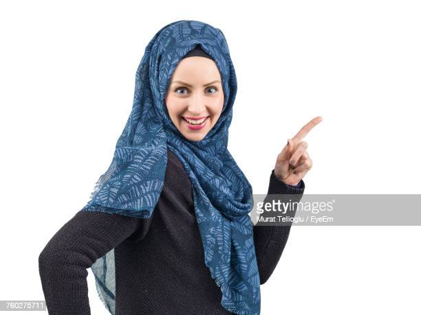 Portrait Of Smiling Young Woman In Hijab Pointing Against White Background