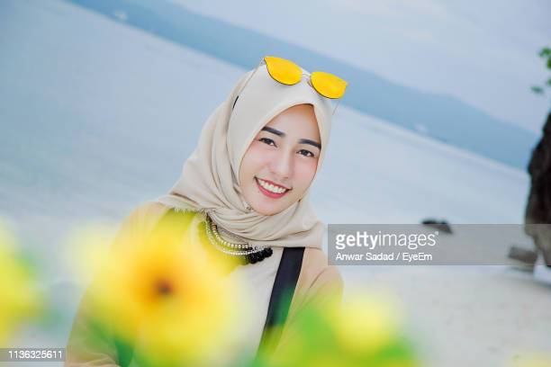 Portrait Of Smiling Young Woman In Hijab Standing At Beach