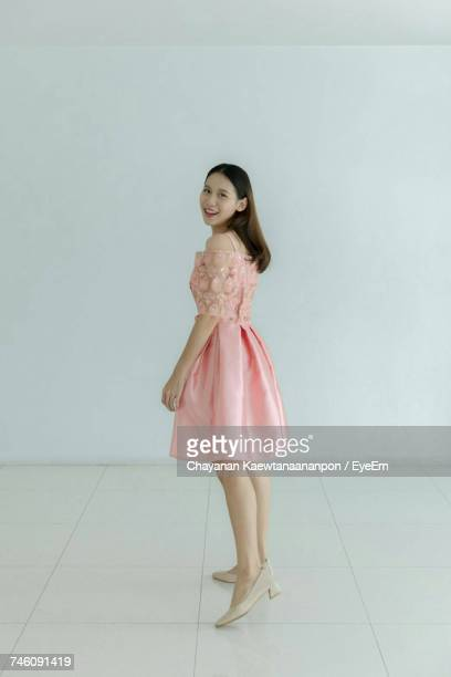 portrait of smiling young woman in pink dress standing against wall at home - pink dress stock pictures, royalty-free photos & images