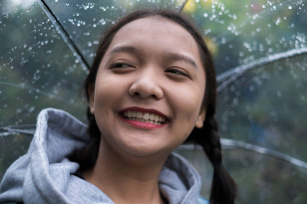 Portrait Of Smiling Young Woman In Rain