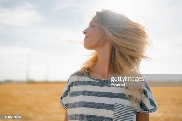 portrait of smiling young woman in rural landscape - einfaches leben stock-fotos und bilder