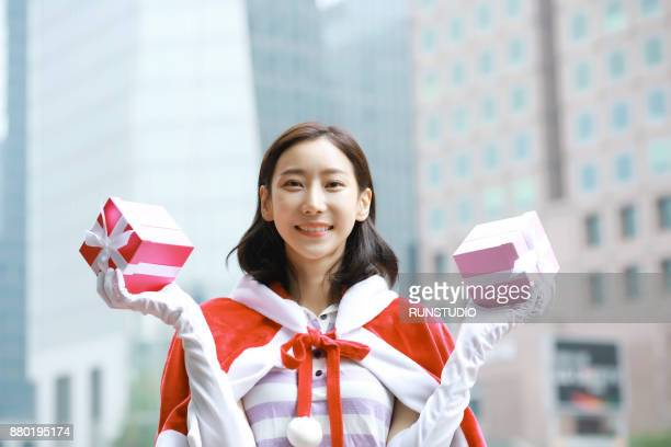 portrait of smiling young woman in santa claus cloak holding gift boxes - evening glove stock pictures, royalty-free photos & images