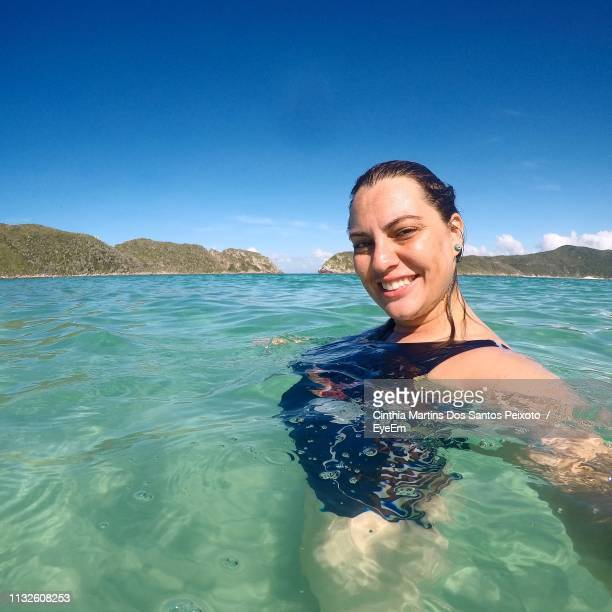 Portrait Of Smiling Young Woman In Sea Against Sky