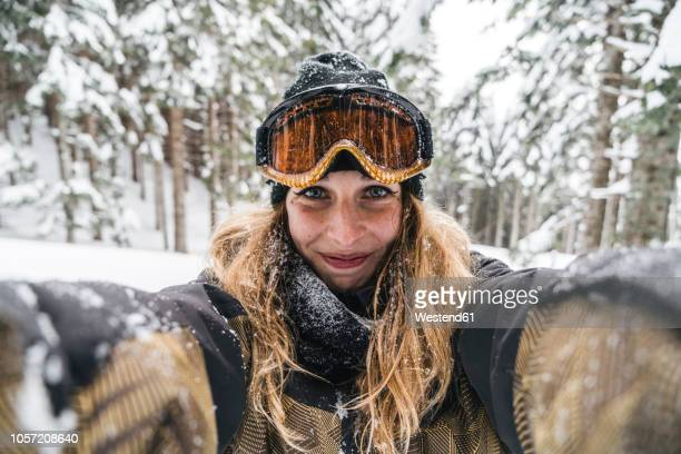 portrait of smiling young woman in skiwear in winter forest - wintersport stockfoto's en -beelden