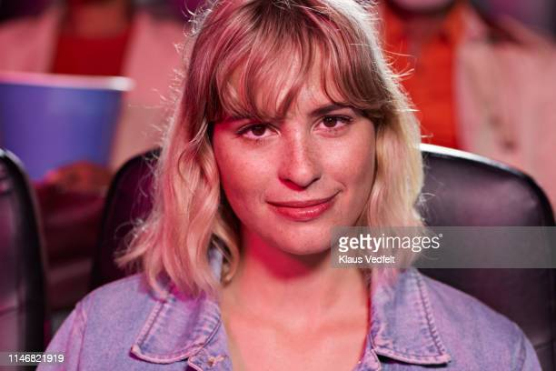 portrait of smiling young woman in theater - mittellanges haar stock-fotos und bilder