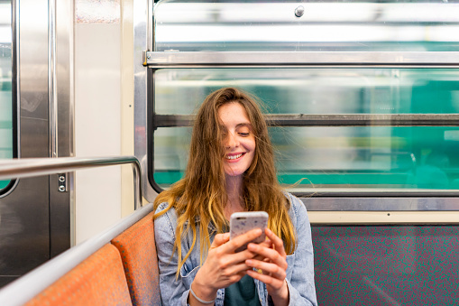 Portrait of smiling young woman in underground train looking at smartphone - gettyimageskorea