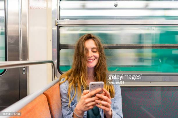 portrait of smiling young woman in underground train looking at smartphone - french women stock photos and pictures