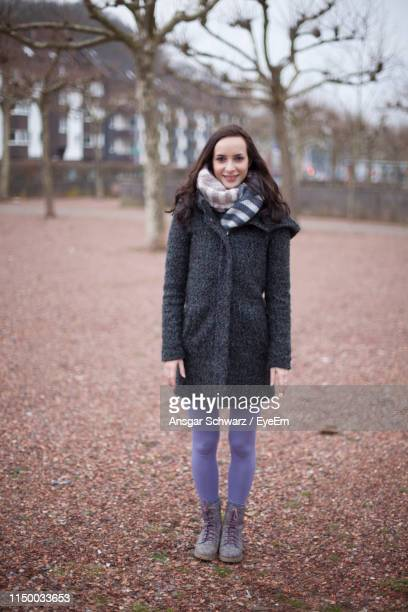 portrait of smiling young woman in warm clothes standing outdoors - winter coat stock pictures, royalty-free photos & images