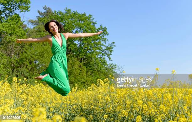 portrait of smiling young woman jumping at oilseed rape field - green dress stock pictures, royalty-free photos & images