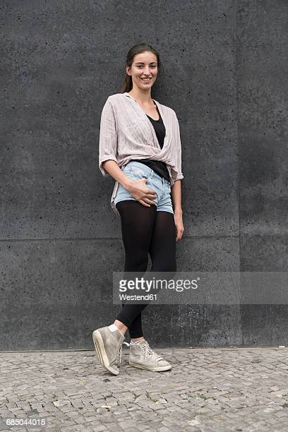 Portrait of smiling young woman leaning against wall