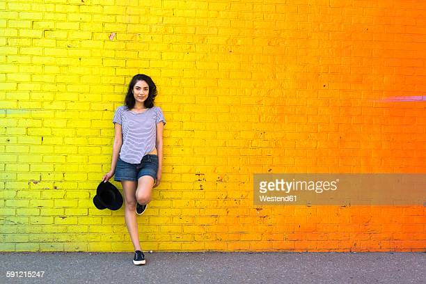 portrait of smiling young woman leaning against yellow brick wall - levendige kleur stockfoto's en -beelden