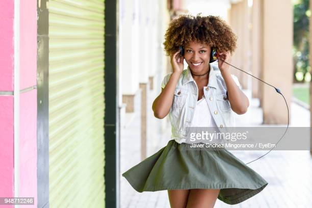 portrait of smiling young woman listening to music at corridor - black skirt stock pictures, royalty-free photos & images