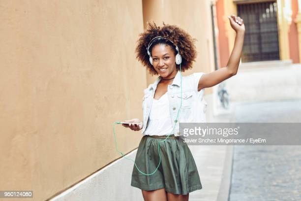 portrait of smiling young woman listening to music on sidewalk - black skirt stock pictures, royalty-free photos & images