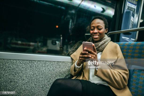 Portrait of smiling young woman looking at cell phone in underground train