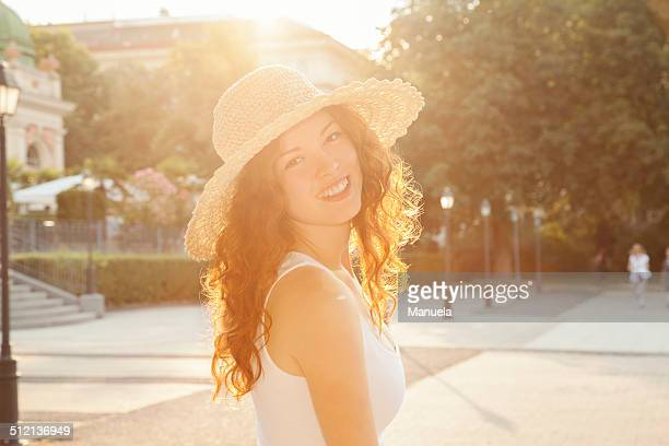 Portrait of smiling young woman looking over her shoulder in city