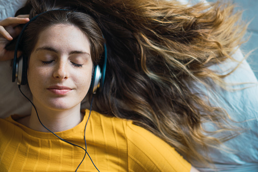 Portrait of smiling young woman lying on bed listening music with headphones - gettyimageskorea