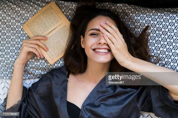portrait of smiling young woman lying on bed with a book covering one eye with her hand - bettwäsche stock-fotos und bilder