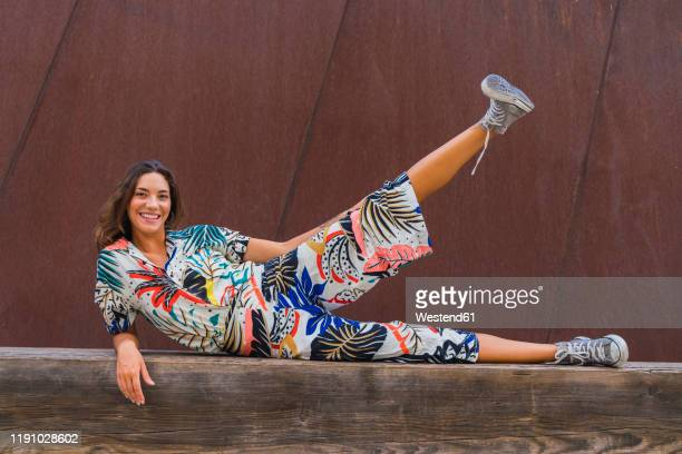 portrait of smiling young woman lying on wooden bench lifting leg - lying on side stock pictures, royalty-free photos & images