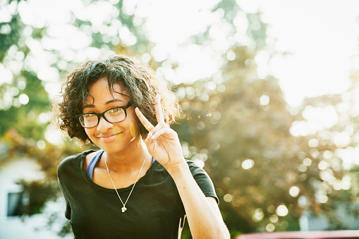 Portrait of smiling young woman making peace sign with fingers on summer evening - gettyimageskorea