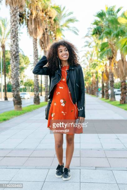 portrait of smiling young woman on a promenade listening music with earphones and smartphone - leather dress stock pictures, royalty-free photos & images