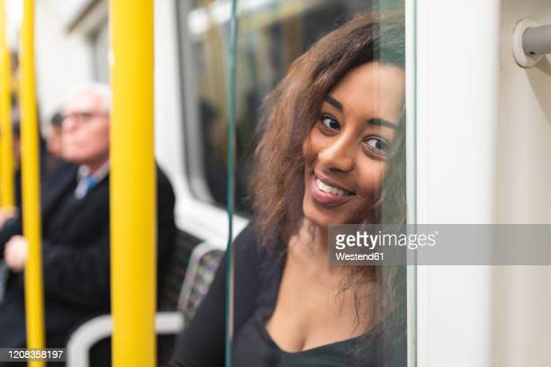 portrait of smiling young woman on a subway - bahnreisender stock-fotos und bilder