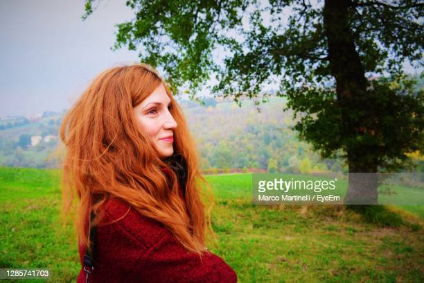 portrait of smiling young woman on field - martinelli stock pictures, royalty-free photos & images