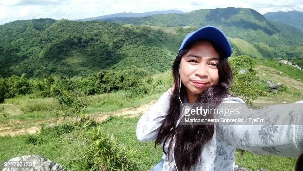 Portrait Of Smiling Young Woman On Mountain
