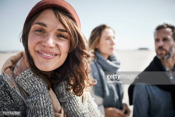 portrait of smiling young woman on the beach with people in background - drei personen stock-fotos und bilder