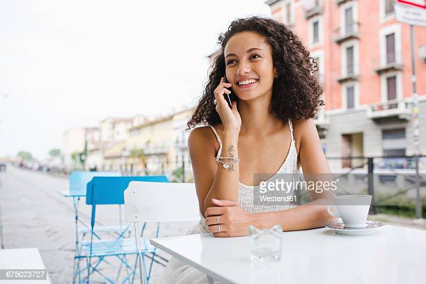 Portrait of smiling young woman on the phone at sidewalk cafe