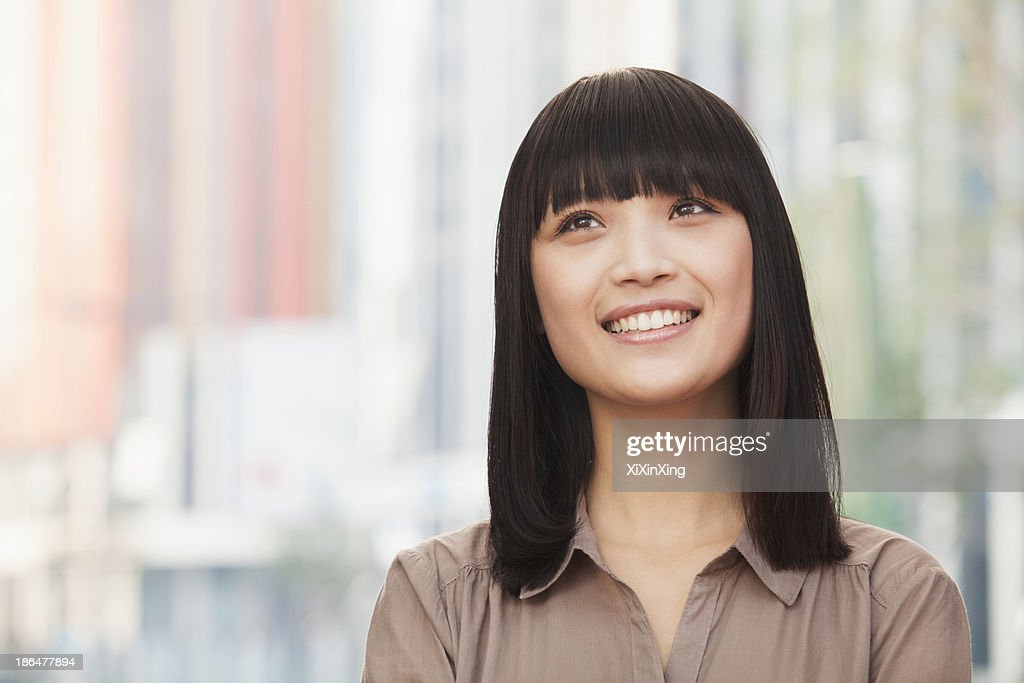 Portrait of smiling young woman outdoors in Beijing, looking up : Stock Photo
